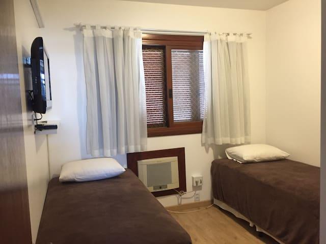 Quarto com duas camas de solteiro, TV, ar condicionado e armários.