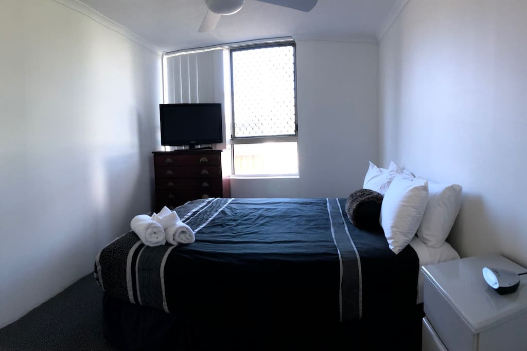 Main bedroom with TV and ceiling fan.