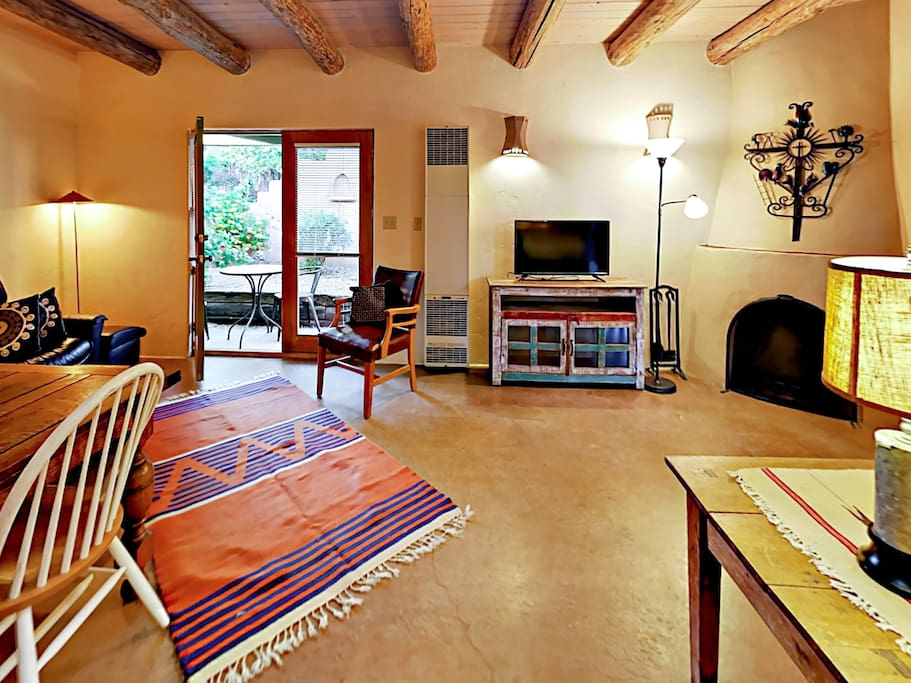 With a kiva wood-burning fireplace and exposed beams, the main living area embodies classic Santa Fe charm.