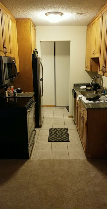 Kitchen area, with full appliances - microwave, oven/stove and dishwasher.