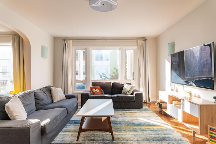 """Sunny living room with super comfortable couches and 60"""" TV."""