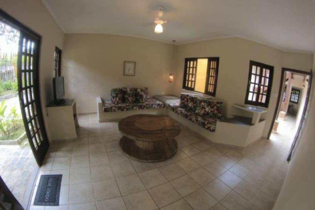 Sala ampla com TV a cabo e sofás de alvenaria bem confortáveis