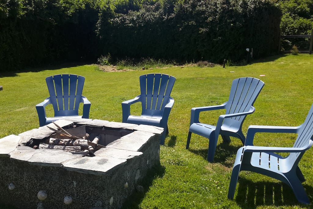Large fenced and gated yard with fire pit.