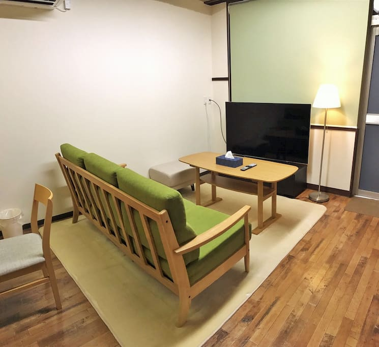 Living room with a 58-inches television, with a sofa and a cushion that allow 4-6 people to sit together.