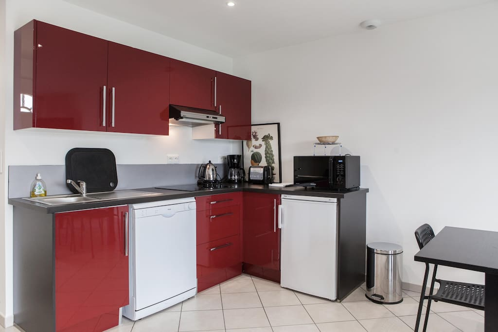 la cuisine est équipée d'un combiné four micro onde, d'un lave vaisselle, d'un refrigerateur, d'une plaque vitro céramique, d'une cafetiere, d'une bouilloire, d'un grille pain et de la vaisselle et ustensiles