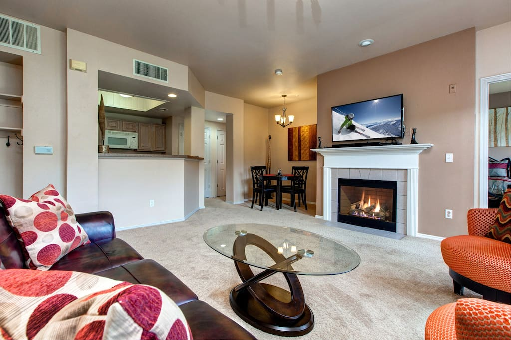 Wide living area with fireplace and flatscreen TV.