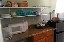 Small refrigerator with freezer, microwave and coffee maker, dishes, glasses, cups, silverware and everything else you need.