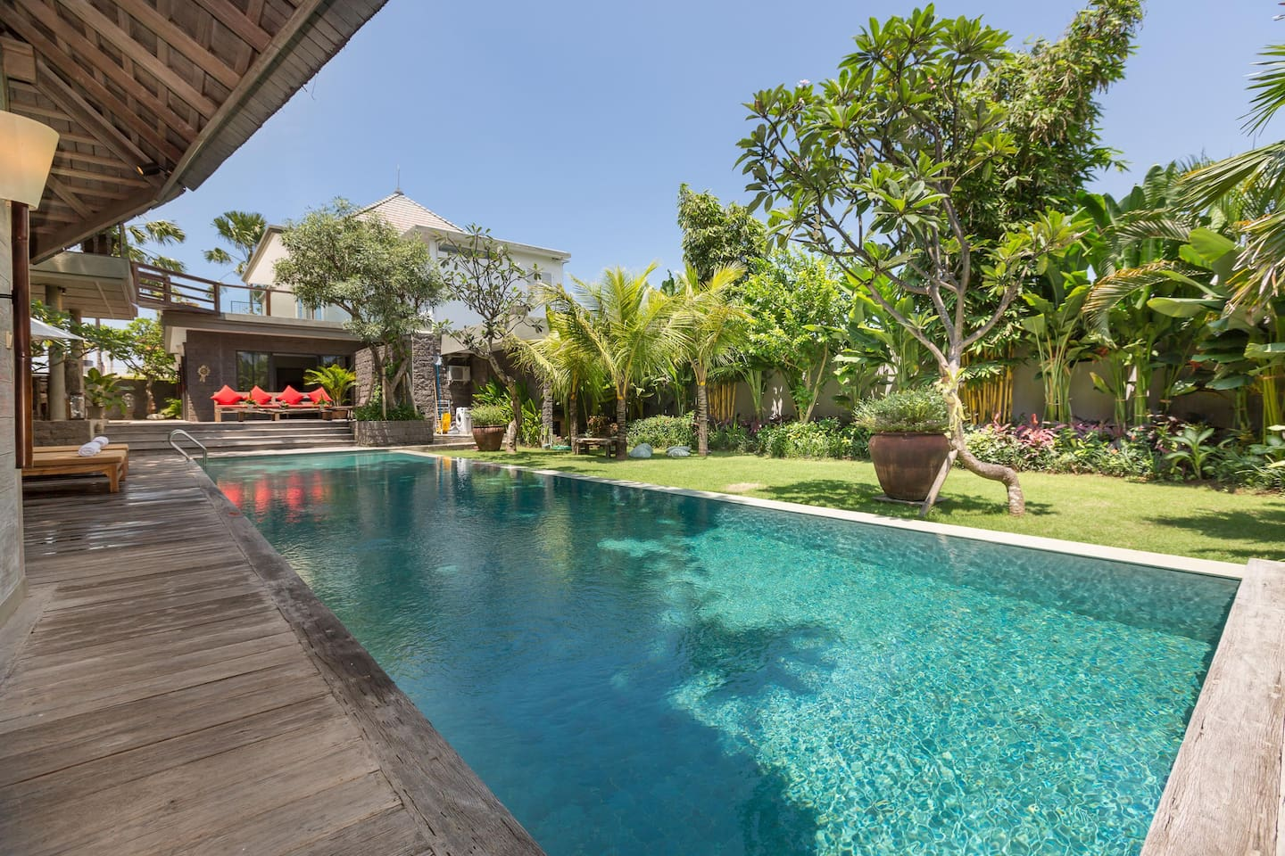 The main swimming pool surrounded by sundecks and green garden