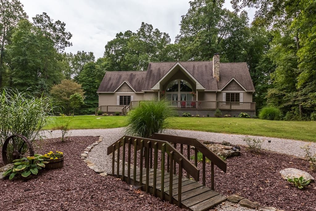 Country home surrounded by trees, with inviting circle drive.