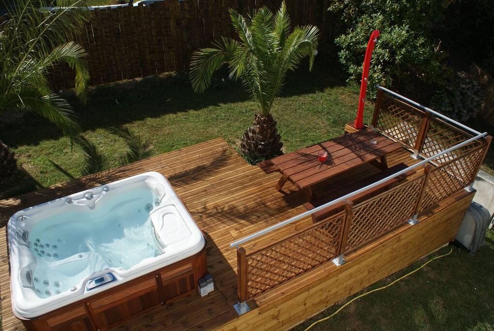 Spa de trois places SUNDANCE/USA sur terrasse en bois et douche solaire face aux Pyrénées