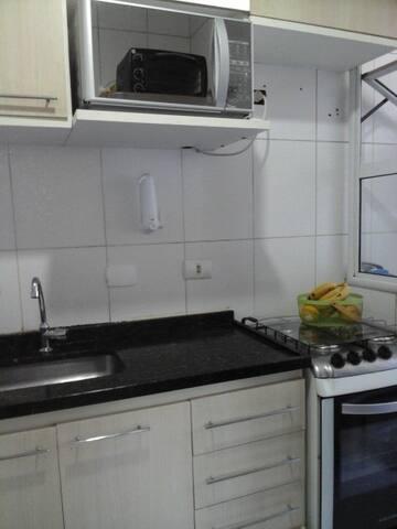 Cozinha compartilhada com fogão, micro ondas, forno elétrico e geladeira