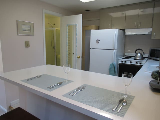 Kitchen has a full refrigerator, stove, oven, microwave, and sink.  Bathroom door on left.