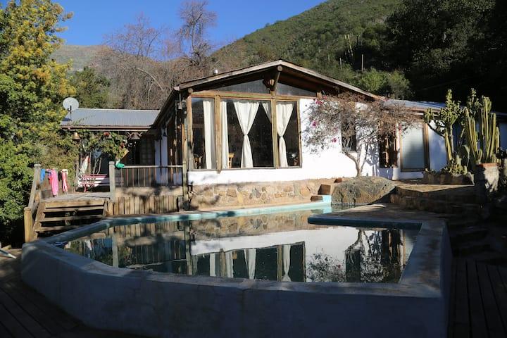 Casa de campo rodeada de cerros y naturaleza.