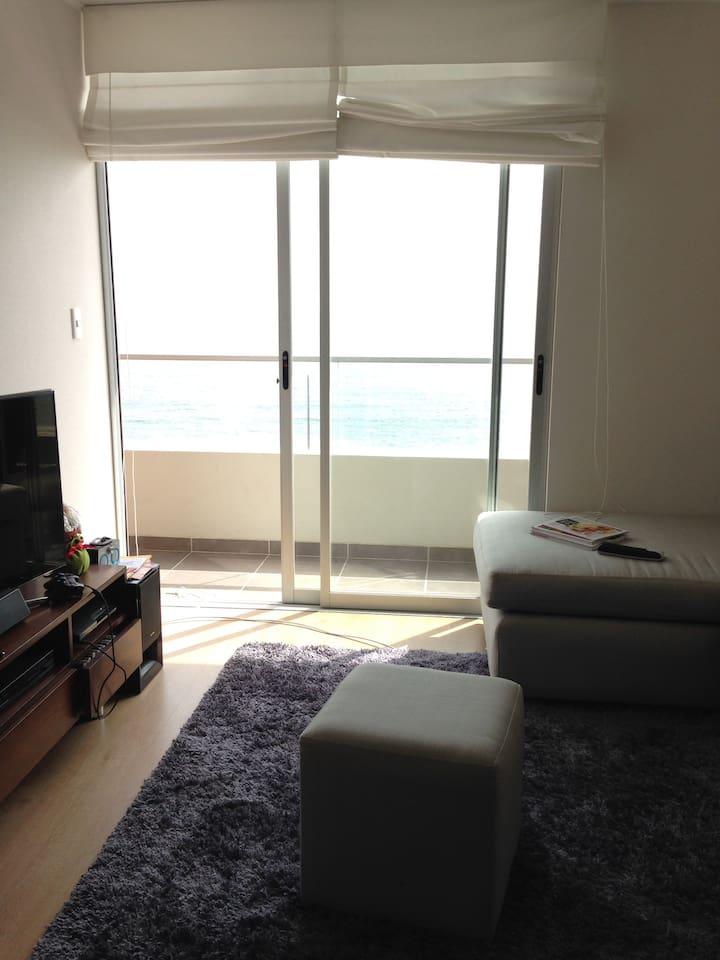 Foto de la sala con vista al mar, así como el dormitorio.