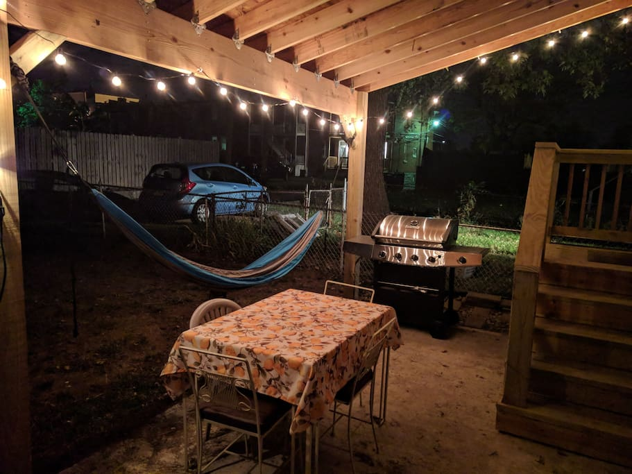 Fenced in backyard with covered area including hammock, gas grill, fire pit and dining area.