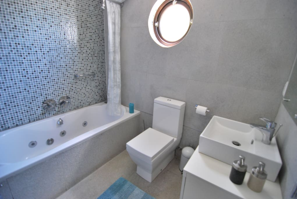 The bathroom is modern with shower/bath/jacuzzi