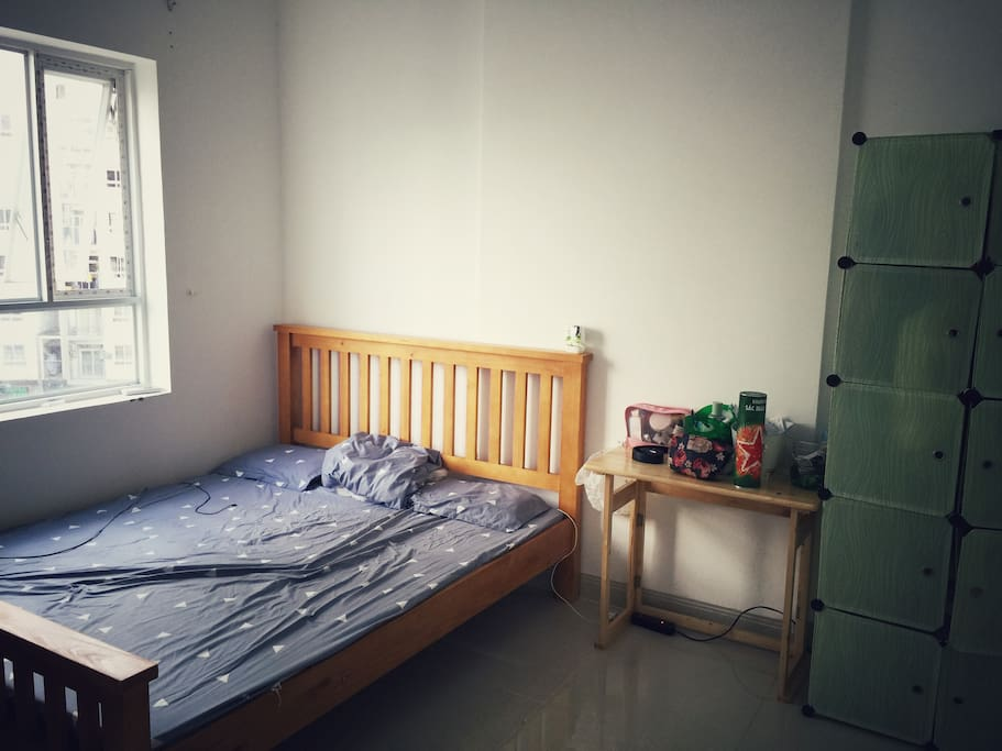 Bed room with double bed next to a bright window