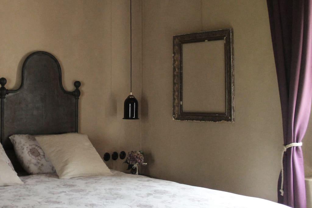 antica testiera in ferro tra lampade in vetro di Murano