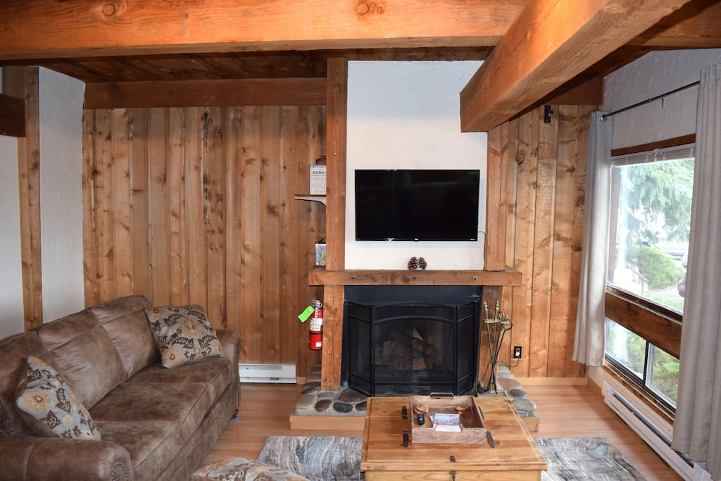 The living room area from the entryway. Big, comfy couches, Roku Smart-TV and wood-burning fireplace!