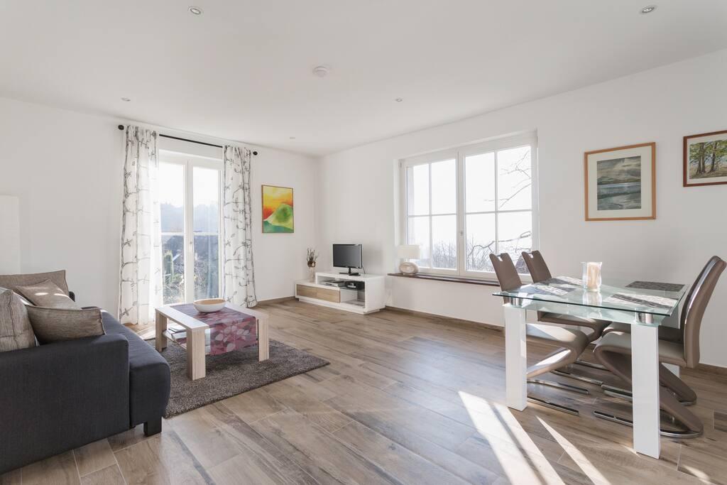 Helles Wohnzimmer mit Fußbodenheizung und Ausgang zut Terrasse und Garten