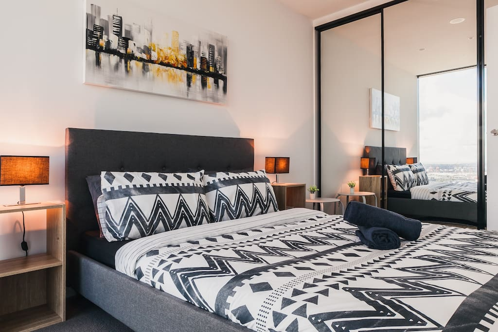 Well appointed bedroom with queen size bed, floor to ceiling glass panel closets and amazing views