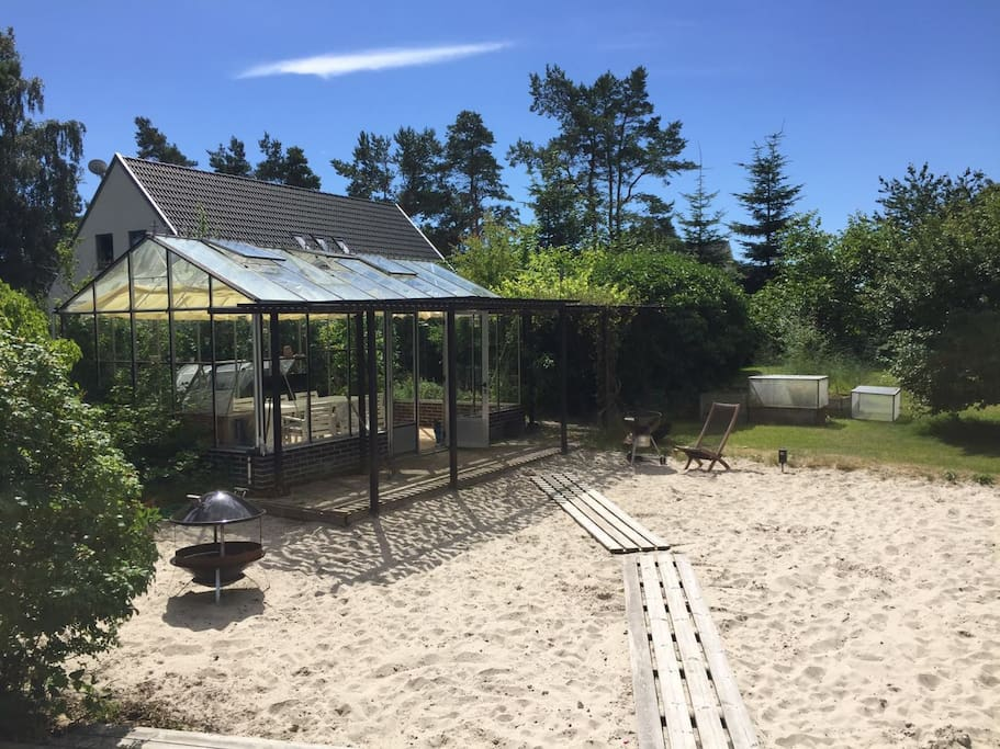 """""""Beach"""" in the garden with a greenhouse built for late night dinners"""