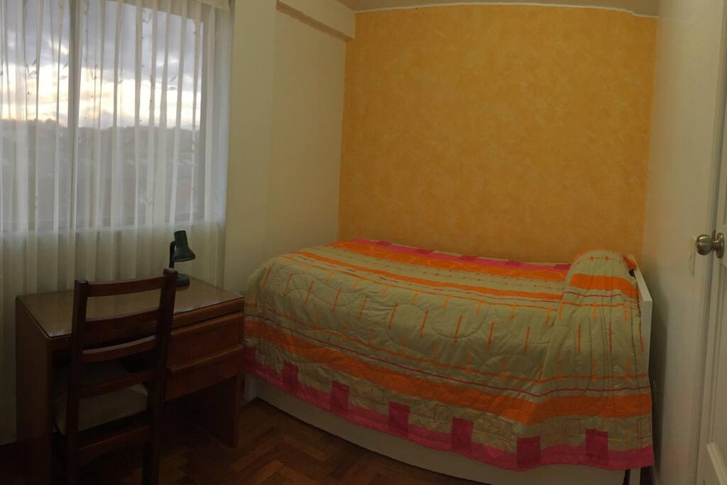 Habitación con cama de plaza y media y una cama auxiliar