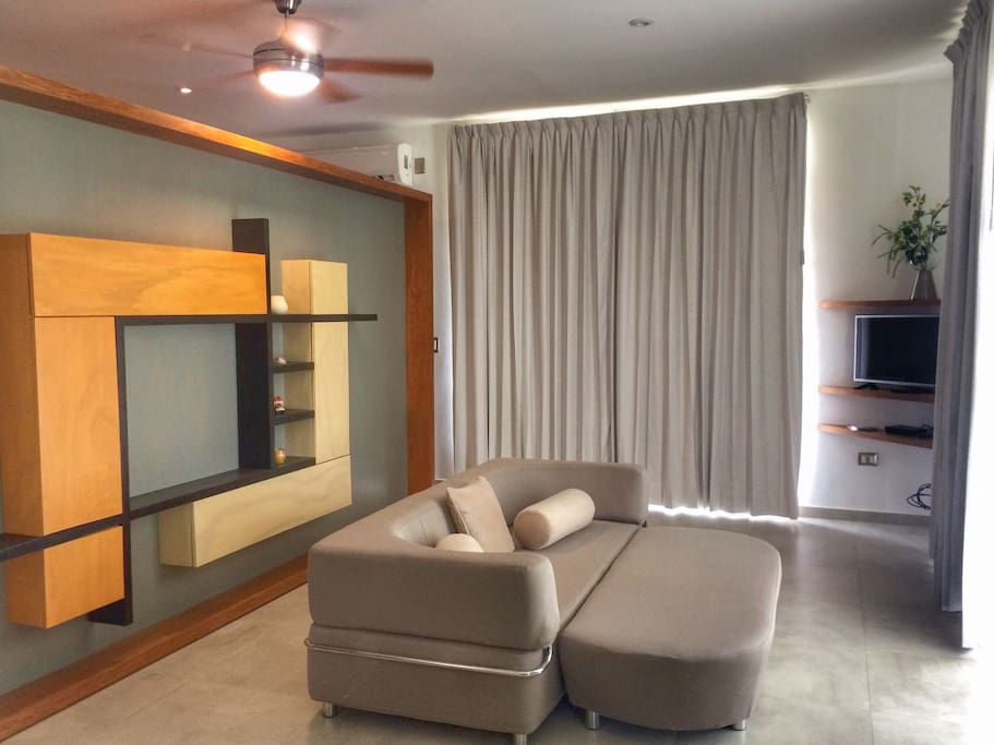 The living room area with modern furniture, a comfy sofabed and TV.