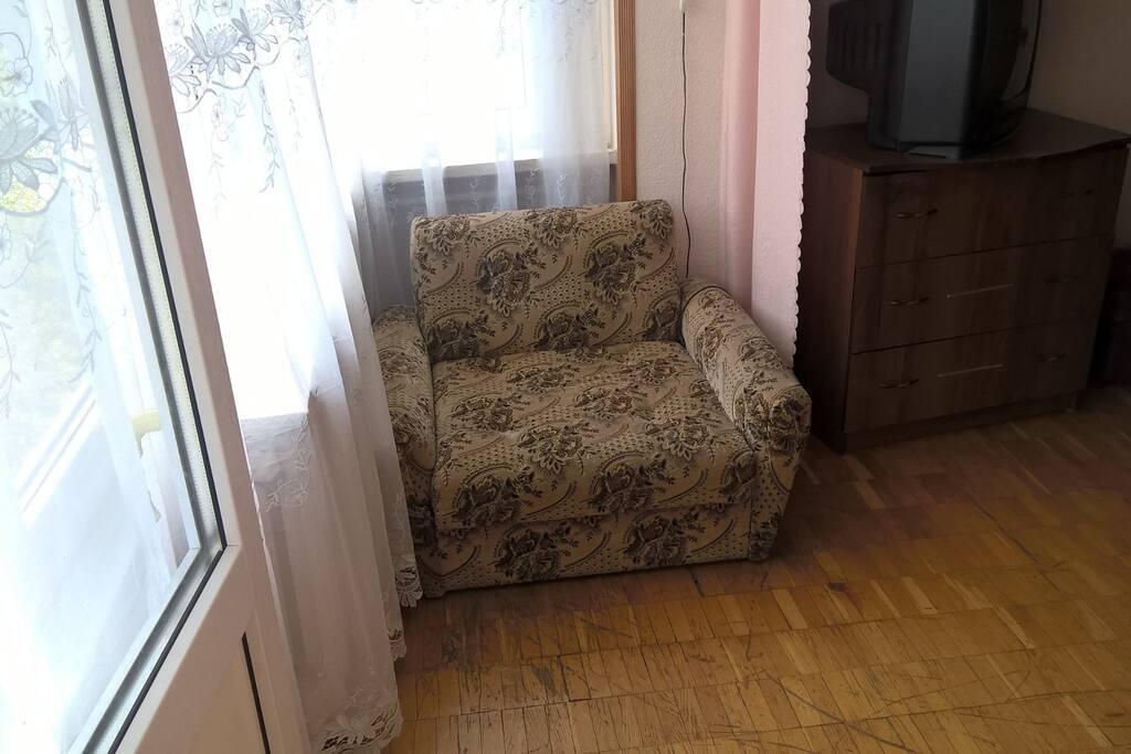 Это небольшая лоджия с мягким раскладным креслом. Окна выходят во двор. С лоджии есть выход на балкон.
