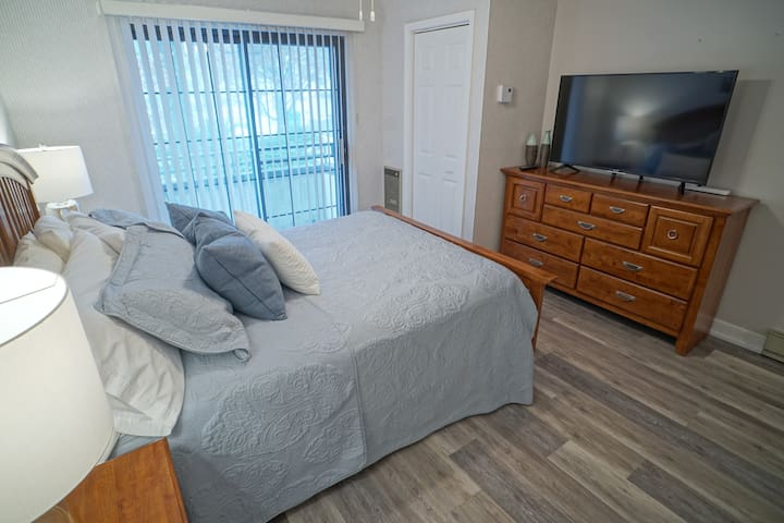Master suite with queen bed, balcony and large TV
