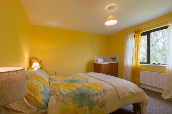 The recently painted yellow room has a queen bed and a view over the back fields towards the sea.