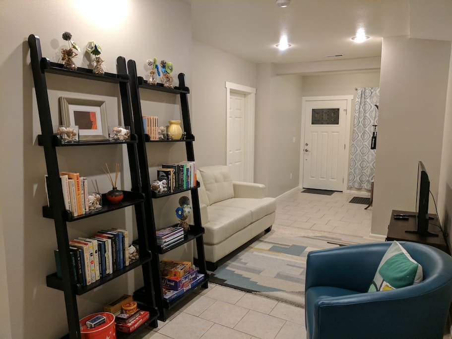 Living area includes a couch, swivel chairs, TV, and bookshelves. We've provided reading materials and games for nights in. Ottomans can be moved around the unit for extra seating as needed.