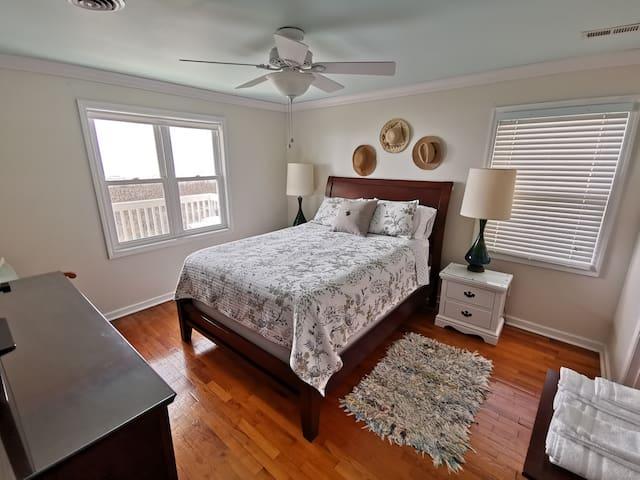 Ocean view bedroom with queen size bed and tv