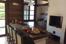 Área de churrasqueira equipada com fogão e uma ampla e confortável mesa de refeições