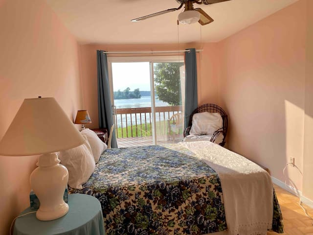 The primary bedroom has a queen size bed, dresser, desk and walk out to the deck.