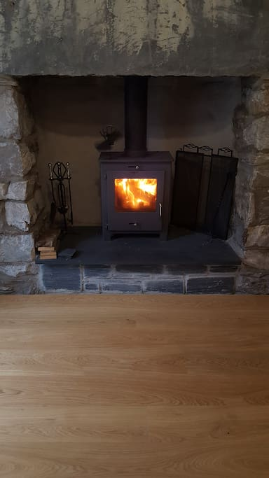 The living room has a wood-burning stove and an oak floor
