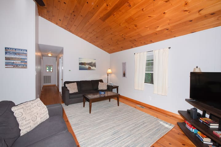 Living room has heart of pine flooring and ceiling.  With sleeper sofa and loveseat, TV, and tables, this opens onto large deck with water views.