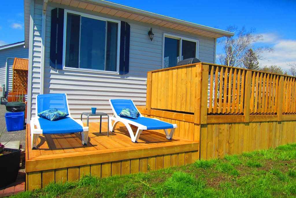 a fab deck with loungers and a dining area with BBQ