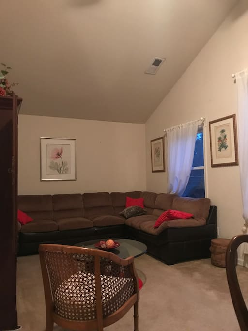 Living room area with cathedral ceiling, large mahogany desk, ceiling fan with light and programmable controls, large windows and closets, double sofa, coffee table, wall to wall carpet, and WIFI.