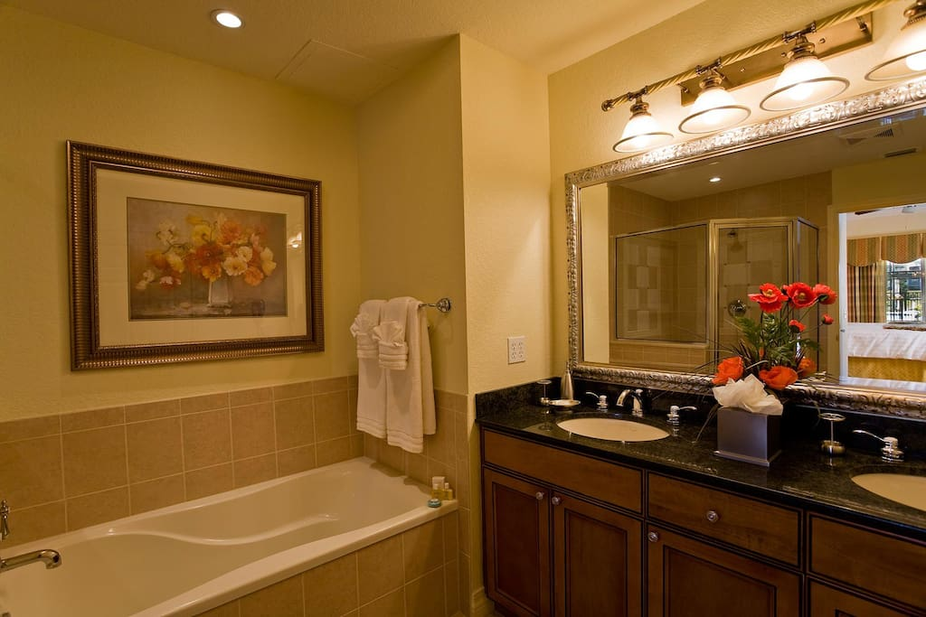Suite 1 private bathroom with two sinks, bathtub & glass door shower