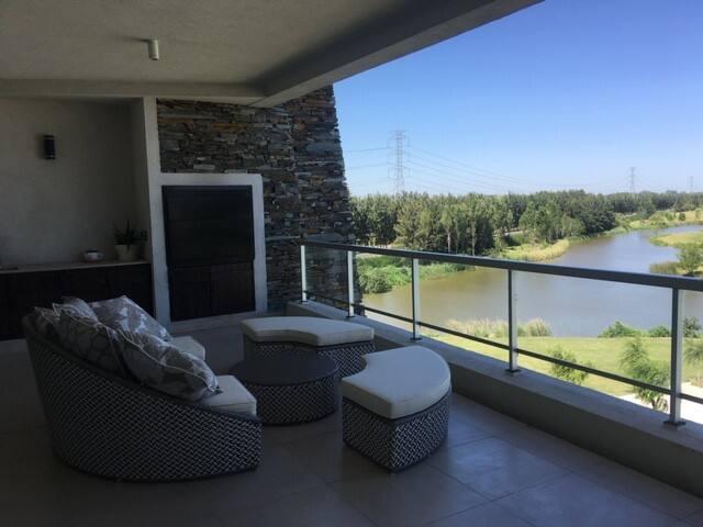 Amplio balcón aterrazado con parrilla y vista al lago, campo de golf  y piscinas