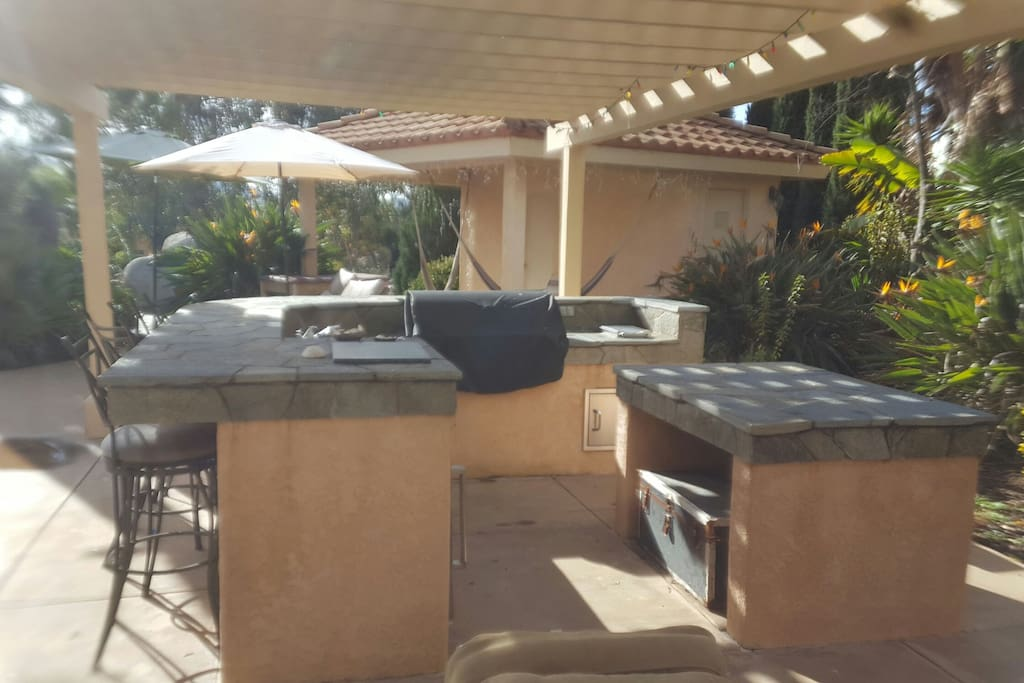 Outdoor gourmet kitchen with built in barbecue sink and refrigeration. Built for outdoor grill days in a very private setting.