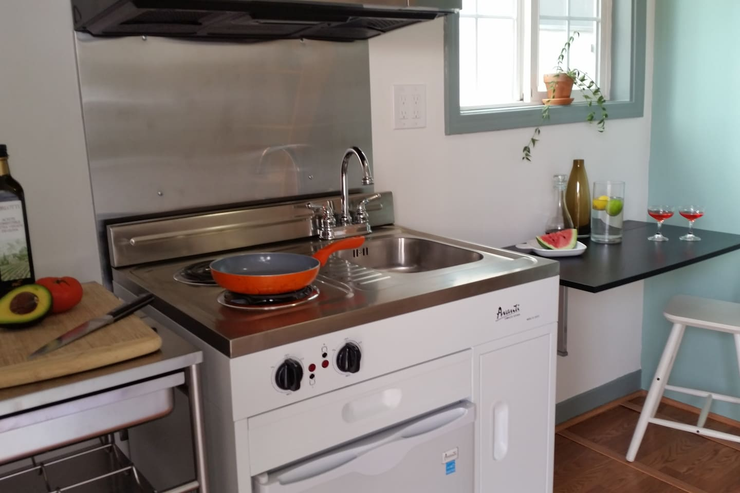 Kitchen unit with two-burner stove, sink, pantry, mini refrigerator and full size microwave.