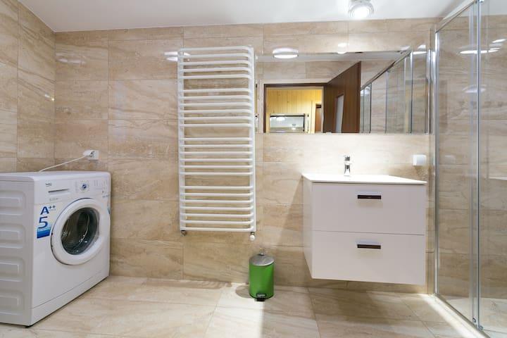 łazienka z pralką suszarka i umywalką