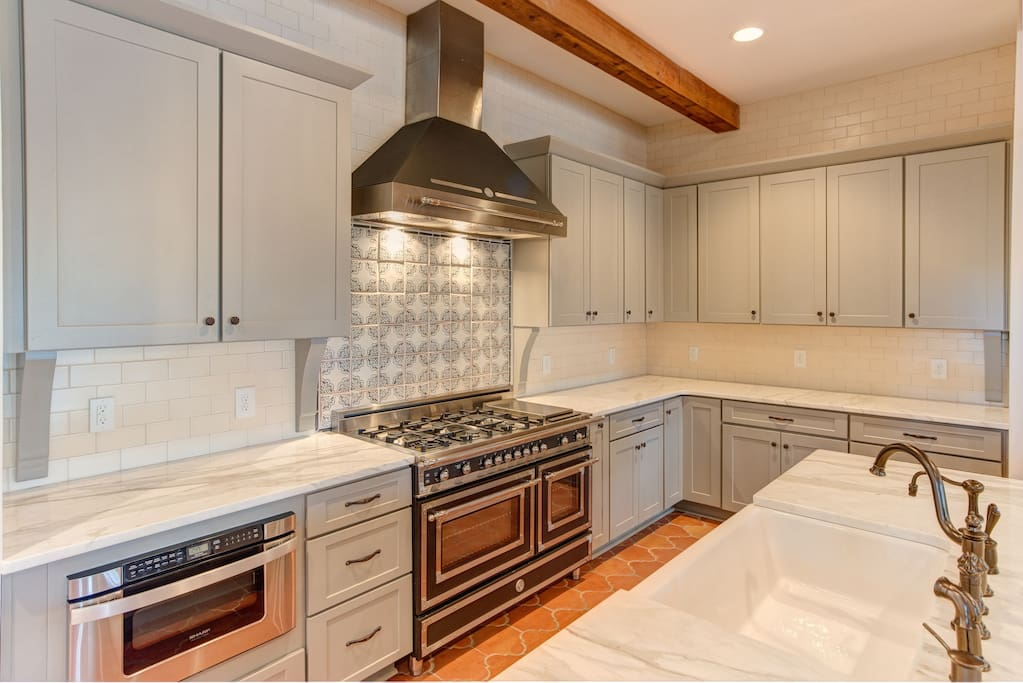 Custom cabinets, handmade tile, Italian gas range, high end marble in kitchen.