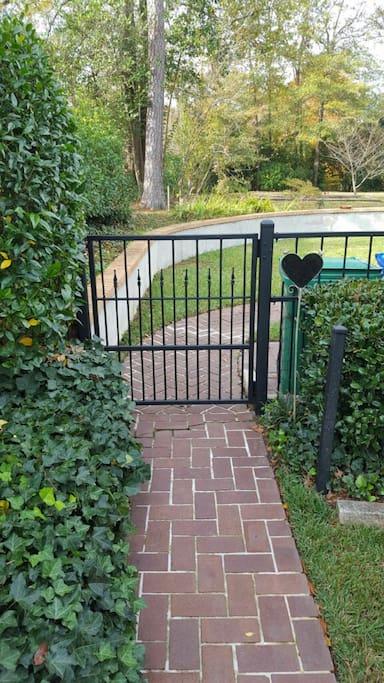 Enter through iron gate into backyard.