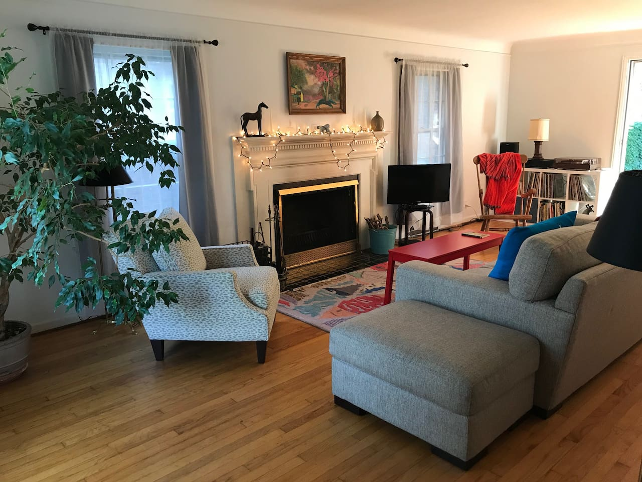 Living room with wood burning fireplace, large sofa, TV with Hulu and HBO, and sound system with turntable and wireless device play.
