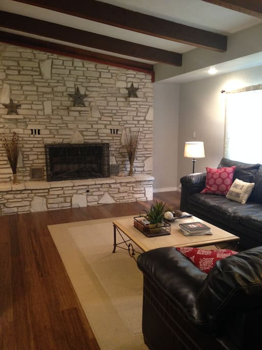 Living room with beamed ceiling, rock fireplace, and wood floors