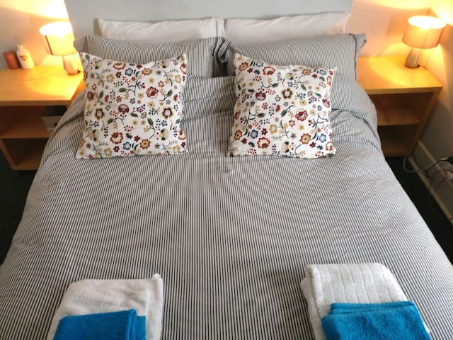 Comfortable, quiet, heated bedroom with comfortable queen bed and luxurious bedding