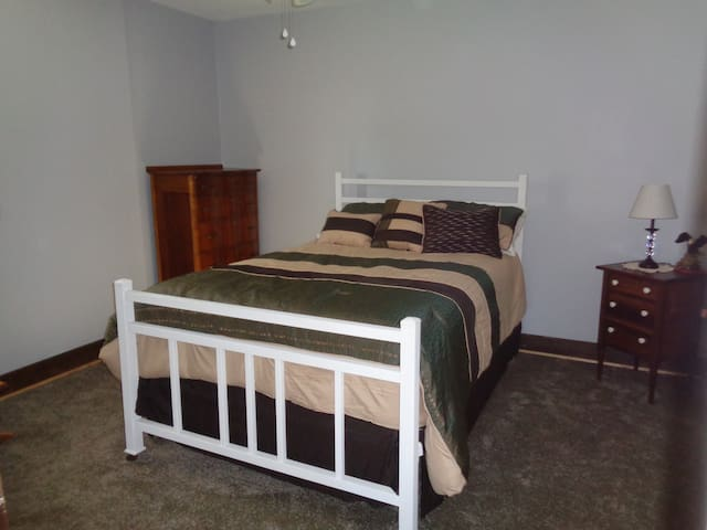 Bedroom 1- full size bed with ceiling fan, rocker in room and night stand.